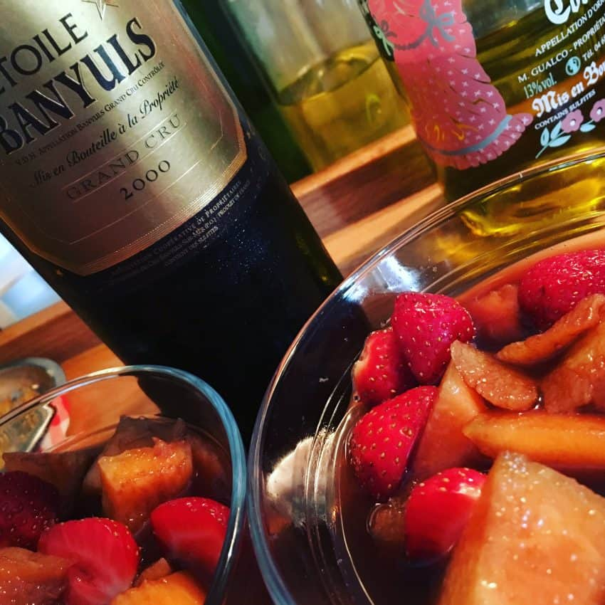 bowls of fruit with bottle of banyols, grand cru