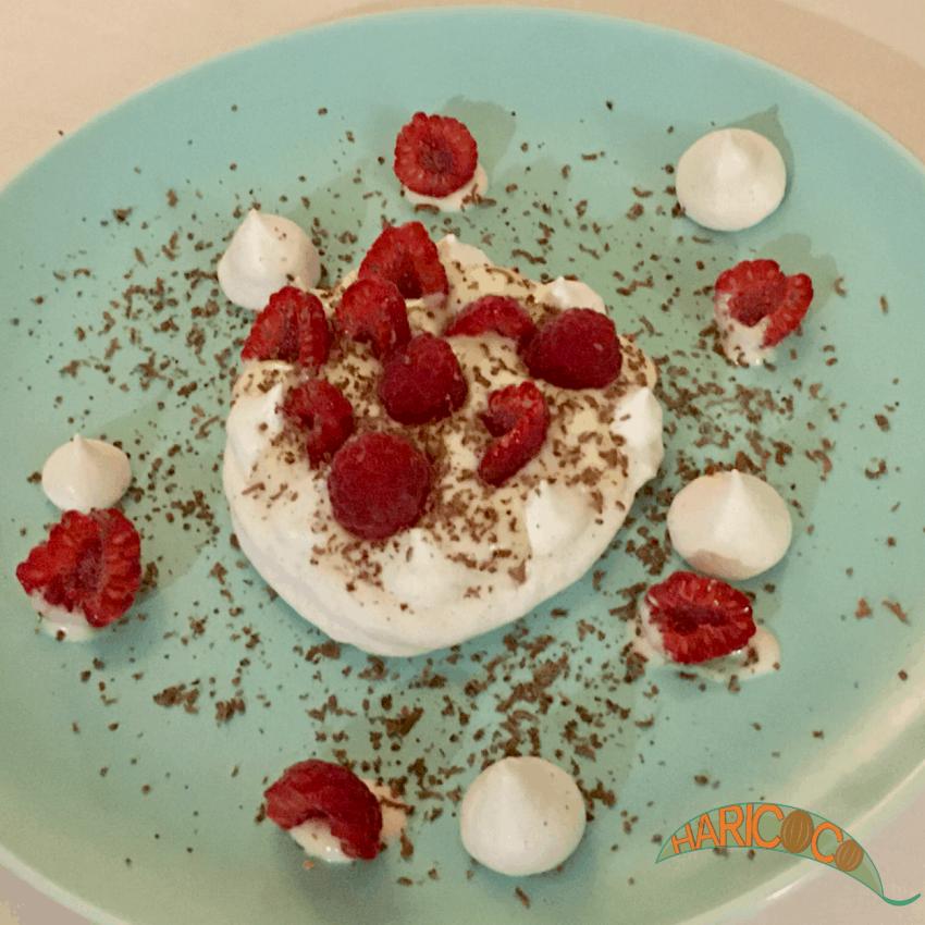 meringues served on plate with raspberries and vanilla yoghurt