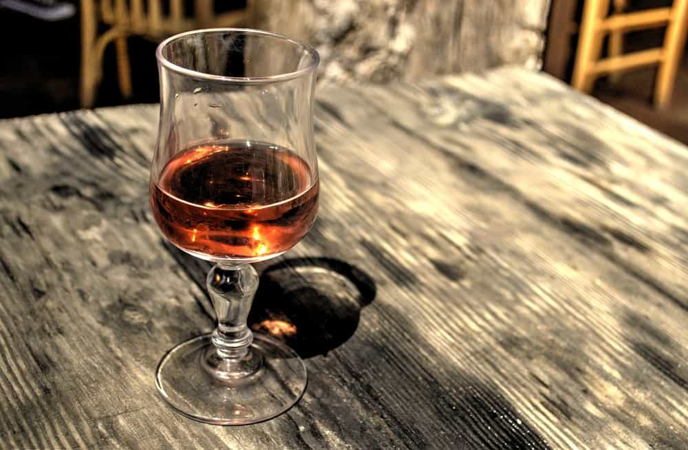 glass of rose on wooden table